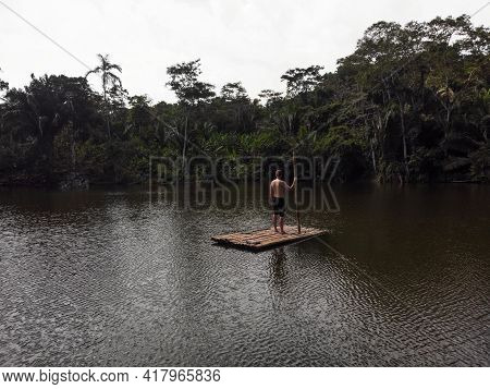 Young Man Standing On Wooden Raft Float On Tropical Exotic Amazon Rainforest Jungle Water Lake River