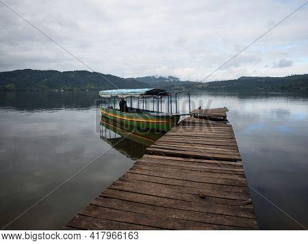 Boat Passenger Ship Vessel Waiting At Idyllic Amazon Rainforest Jungle River Lake Wooden Jetty Dock
