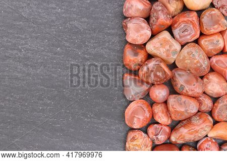 South Onyx Heap Jewel Stones Texture On Half Black Stone Background. Place For Text.