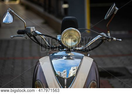 A Vintage  White   Motorcycle, Moped  Stands In A Parking Against The Backdrop Of  Gray Wall. Front