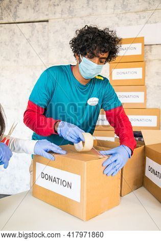 Volunteer Busy Packing Donation Boxes For Donating - Concept Of Charity, Social Work Or Service Duri