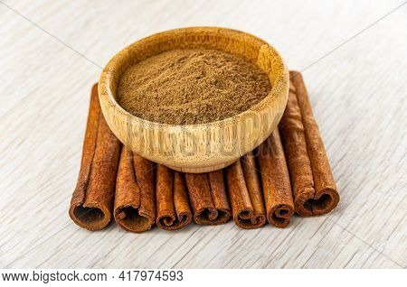 Bamboo Bowl With Ground Cinnamon On Few Cinnamon Sticks On Light Wooden Table