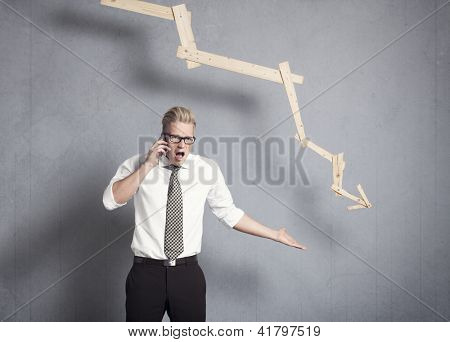 Concept: Business crisis. Enraged young businessman shouting on the phone in front of business graph with negative trend, isolated on grey background.