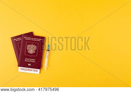 Passports With Vaccinated Stamp On Blank, Syringe With Vaccine On Yellow Background
