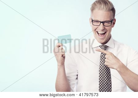 Young cheerful businessman pointing finger at blank business card with space for text while holding it, isolated. poster