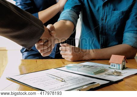 Above View Of Married Couple And Friendly Realtor Shaking Hands After Making Real Estate Deal Indoor