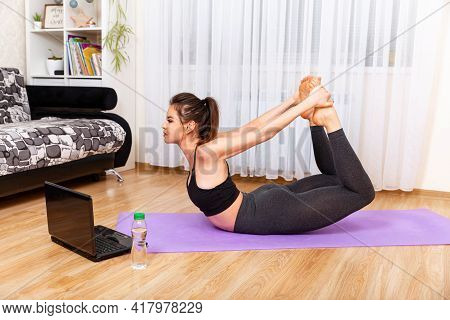 Woman Exercising At Home In Front Of Her Laptop. Achieving Sound Of Mind Through Yoga. Young Sporty