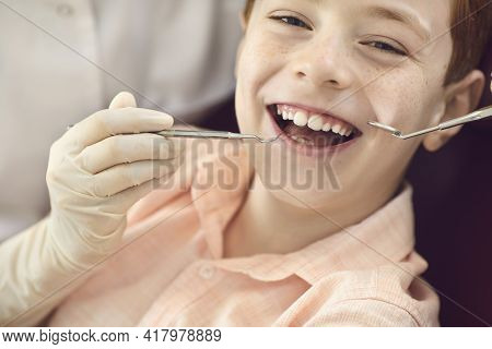 Close Up Portrait Of A Cute Little Boy During Dental Examination And Cleaning Dental Plaque.