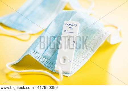 Covid-19 rapid antigen test. Rapid antibodies test kit and surgical face mask on yellow background.
