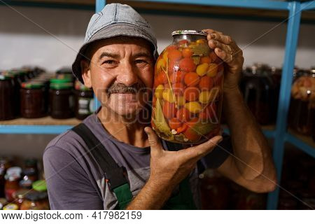 Man Satisfied With The Result Of His Work. He Holds A Glass Jar With Marinated Tomatoes. Fermented O
