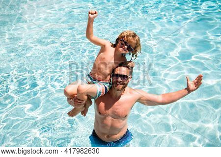Father And Son In Pool. Pool Resort. Boy With Dad Playing In Swimming Pool. Active Lifestyle Concept