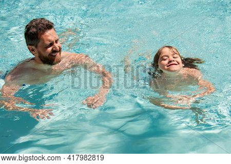 Father And Son In Pool. Summer Weekend. Pool Resort. Boy With Dad Swim In Swimming Pool. Active Life
