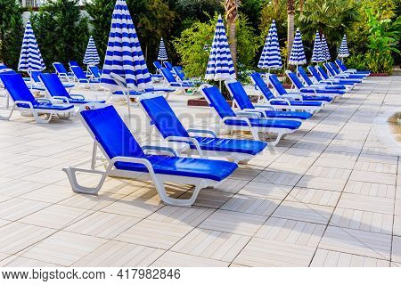 Empty Chaise Lounges And Sun Umbrellas Near Swimming Pool