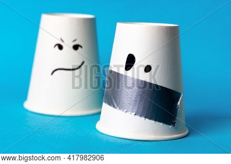 Two Cups With Painted Emotions And A Sealed Mouth. Mouth Sealed With Duct Tape. Freedom Of Speech.