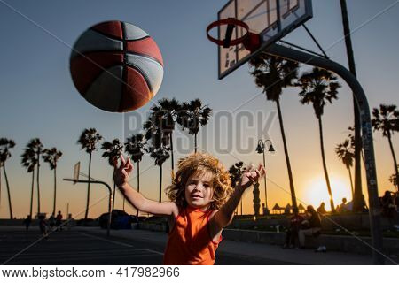 Cute Child Boy Plays Basketball. Active Kids Enjoying Outdoor Game With Basketball Ball On Venice Be