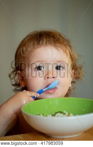 Funny Baby Eating Food Himself With A Spoon On Kitchen. Child Nutrition Concept. Funny Child Face Cl