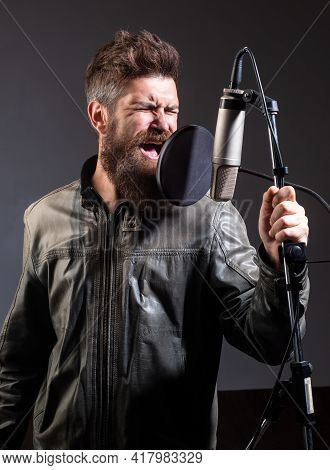 Expressive Singer With Microphone. Singer Wearing Headphones Is Performing A Song With A Microphone