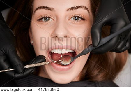 Close Up Of Dentist Hands In Black Sterile Gloves Examining Female Patient Teeth With Dental Mirror