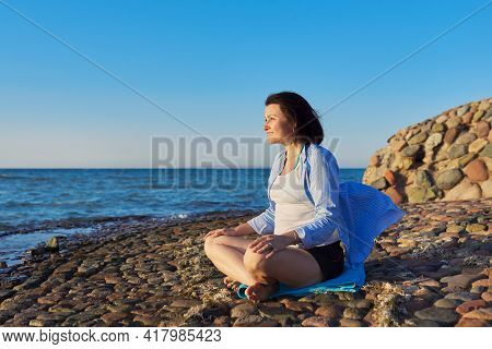 Beautiful Middle Aged Woman Sitting In Lotus Position Meditating On Seashore At Sunset