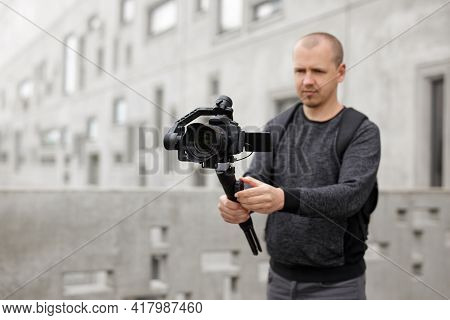 Filmmaking, Videography, Hobby And Creativity Concept - Videographer Shooting Video Using Modern Dsl
