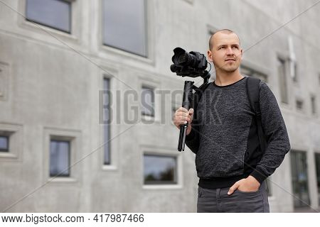 Portrait Of Professional Male Videographer Posing With Dslr Camera On 3-axis Gimbal Stabilizer, Copy