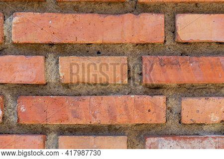 Damaged Brick Wall With Weathered Cracks And Damage Close-up