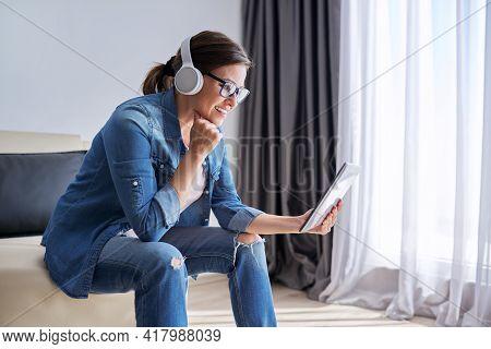 Talking Woman In Headphones Looking Into Digital Tablet Webcam