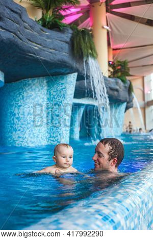 Father With A Baby In The Pool.