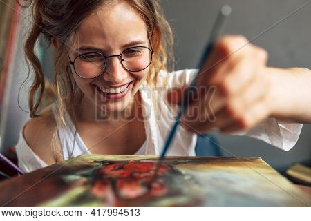 Closeup Of A Pretty Female Artist Painting With A Brush On Canvas In Her Art Studio. A Woman Painter