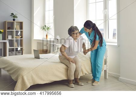 Female Caregiver Who Cares For An Elderly Woman In A Nursing Home Helps Her Get Out Of Bed.
