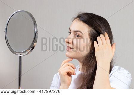 A Brunette Woman 20-30 Years Old Looks In The Mirror And Admires Herself. Self-love, Facial Skin And