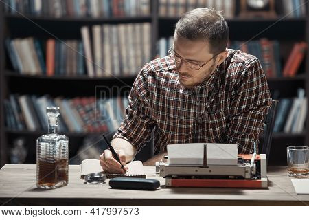 A Young Writer Cleans His Glasses Sitting At A Desk Drinking Alcohol And Writing A Story On A Typewr