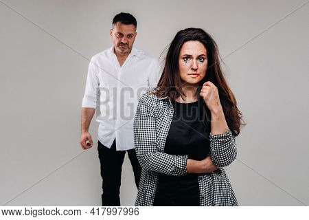 A Woman Beaten By Her Husband Standing Behind Her And Looking At Her Aggressively. Domestic Violence
