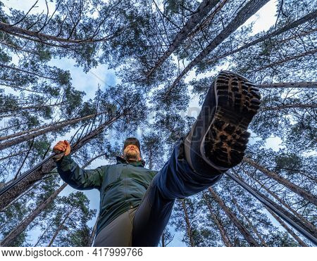 Tourist or sportsman with walking poles in the forest. Nordic walking.