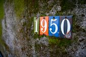 The numbers 1950 are attached to an old wall covered in moss and dirt. poster
