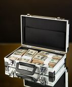 Suitcase with 100 dollar bills on dark color background poster