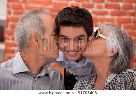 Grandparents kissing their adult grandson