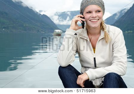 young blond woman called up with her Smartphone with a fjord in Norway in the background poster