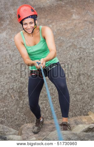 Smiling girl abseiling down rock face looking up at camera