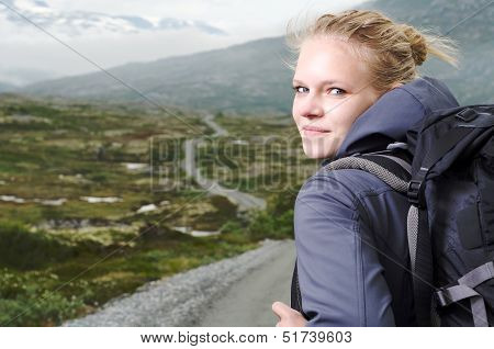young blond woman hiking with scenery in the background poster