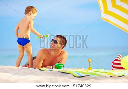 Playful Son Strews Sand On Father, Colorful Beach