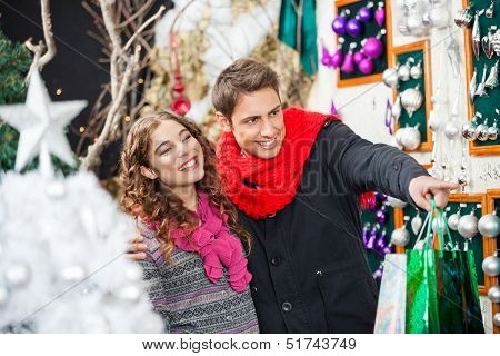 Happy young couple with bags shopping Christmas ornaments at store
