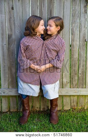 twin girls fancy dressed up pretending be siamese with his father shirt looking each other