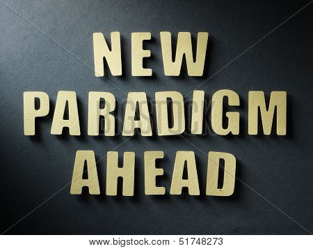 The word New Paradigm Ahead in cut out paper letters on paper background