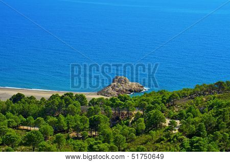 View of Illot del Torn, with the remains of an old watchtower, and Torn Beach, in Hospitalet del Infant, Spain