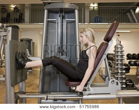 Girl exercing her legs at a health club
