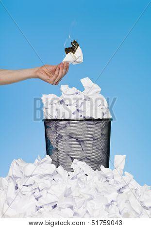 Hand holding unproductive work over a wastebasket