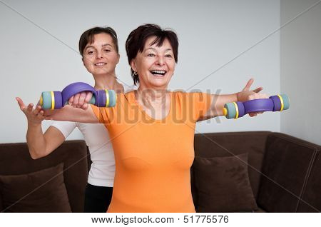 Coach assisting senior woman exercising with barbells