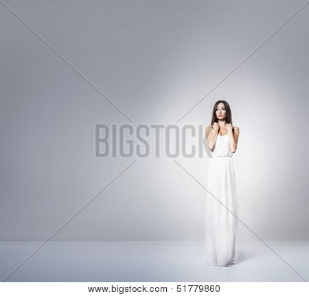 Young and beautiful woman in greek dress over grey background