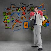 Businessman with boxing gloves standing in front of colored graphics in grey room poster